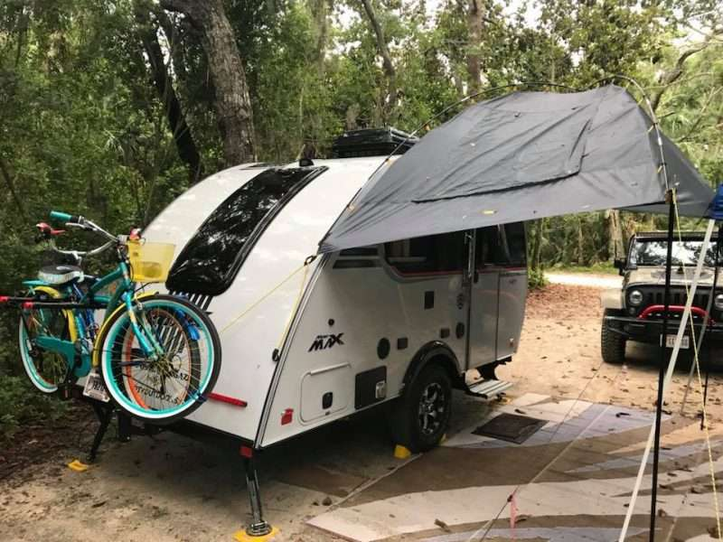 a small camper called the Little Guy Mini Max sits in the woods. There are two bikes mounted on the back of the trailer and an awning over the side provides shade.