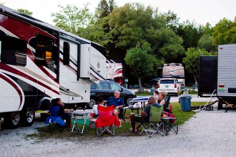 Family members sit on camping chairs around a fire pit at an RV campground.