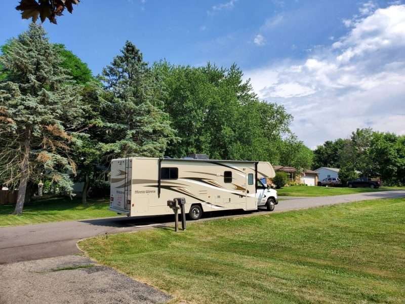 Rving tip: Make sure your RV is road ready before leaving home. An RV sits next to a mailbox in front of a home.