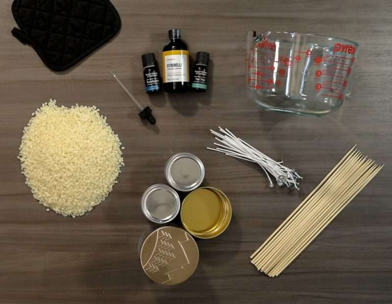 Supplies to make citronella candles are arranged on a wood table. There is a black pot holder, small bottles of citronella and essential oils, an eye dropper, shaved wax bits, empty tin containers, candle wicks, bamboo skewers and a large glass Pyrex measuring cup.