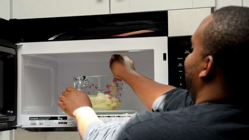 A man melts candle wax in a large glass Pyrex measuring cup using a microwave.