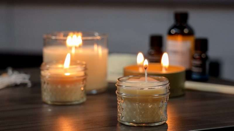 Homemade citronella candles are lit on a wooden table.