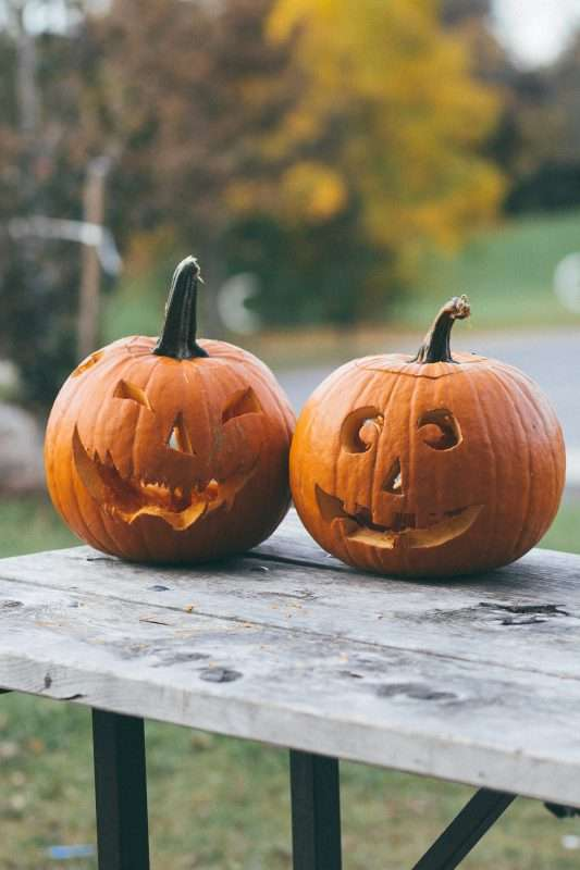 Carving pumpkins is a classic Autumn activity to do. Two pumpkins carved with jack-o-lantern faces sit on a picnic bench table.