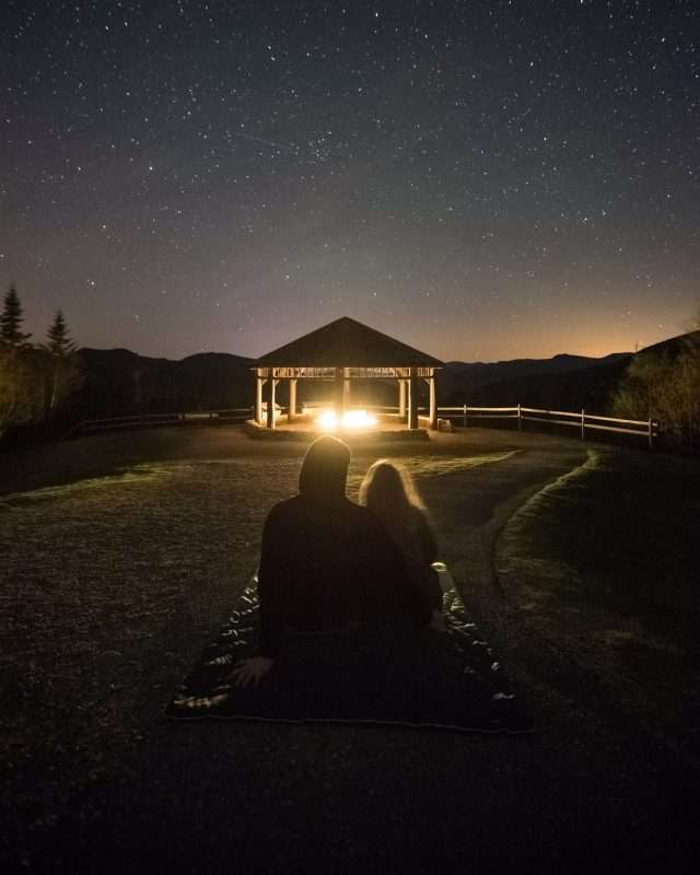 A couple sit together on a blanket viewing the stars of the night sky.