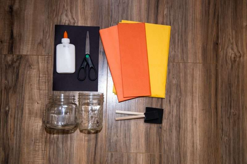 Various shades of orange and yellow tissue paper, scissors, glue, black cardstock, two jars and two small sponge brushes are arranged on a wooden background.