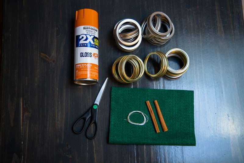 A can of orange spray paint, scissors, green felt, wire, two cinnamon sticks and mason jar lid rings are arranged on a wooden background.