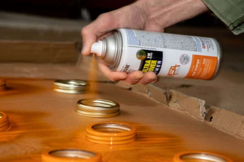A woman spray paints mason jar lids with orange spray paint.