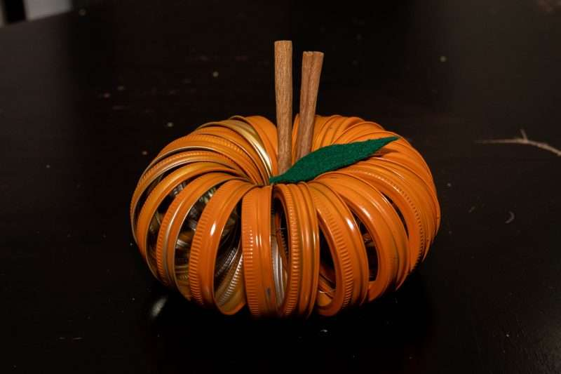 A pumpkin made out of mason jar lids painted orange and strung together with wire.