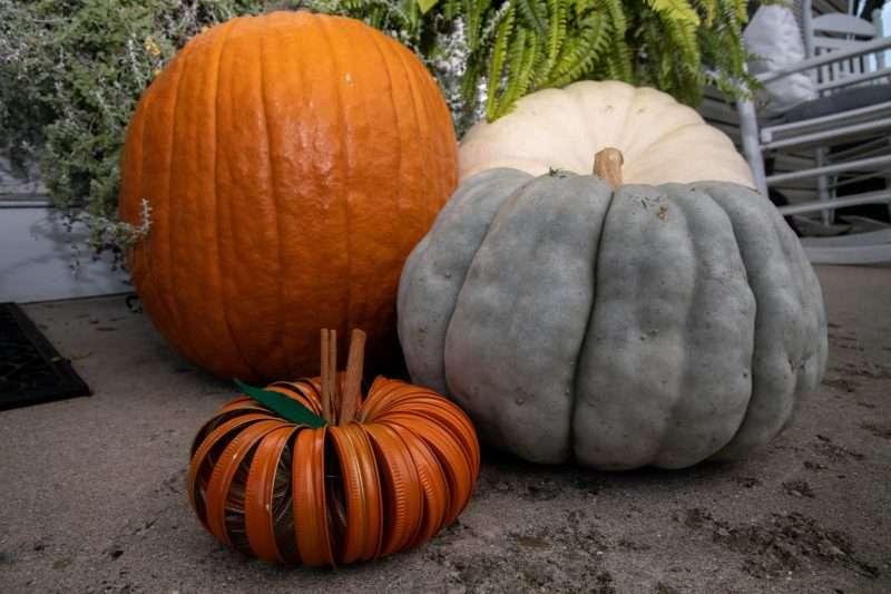 A pumpkin made of mason jar lids strung together sits on a porch next to real pumpkins and squash.