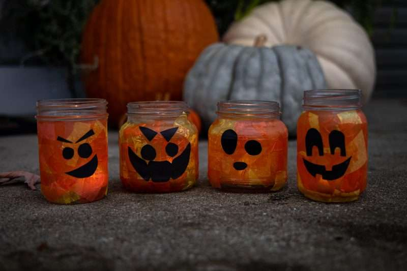 Mason jar pumpkins sit on the ground in front of real pumpkins and squash for a Halloween-themed scene.