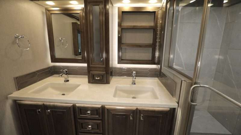 A photo of the Fleetwood Discovery LXE motorhome 40M floorplan master bathroom. This bathroom has a double sink vanity with generous storage and a large walk-in shower.