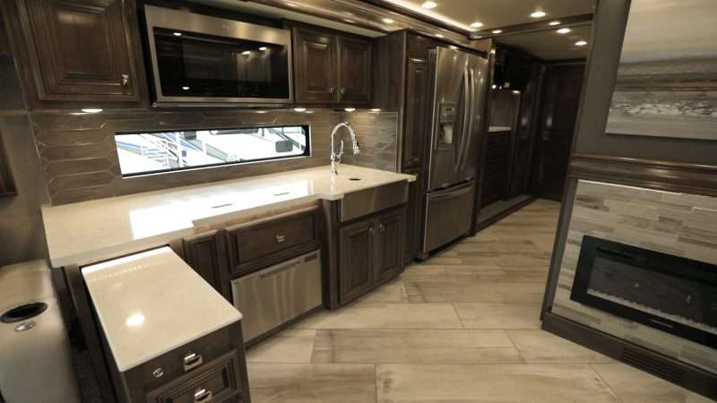 A photo of the kitchen and dining area inside the Fleetwood Di Discovery LXE 40M. This luxurious motorhome a residential size fridge with French doors, a pull-out island for additional counter space, a dishwasher, convection microwave oven, fireplace, and many other high end touches.
