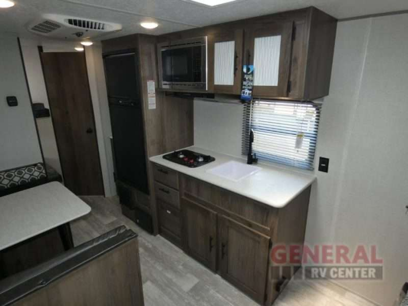 The galley kitchen of the Avenger LT 22BH has a two burner cooktop, sink, microwave and refrigerator with freezer. Across from the kitchen is the booth dining area.
