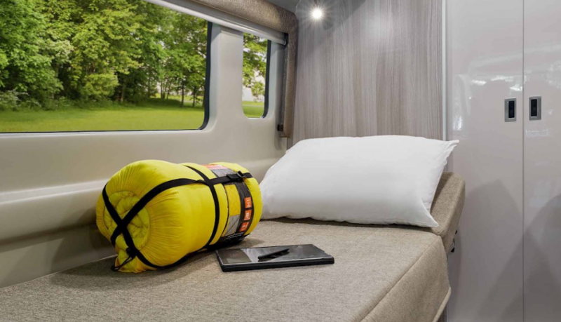 The passenger side couch converted to a bed in the Thor Sequence 20L. A rolled up yellow sleeping bag and tablet with stylus are placed on the bed to emphasize that this is a dual-purpose area. A pillow sits on the adjustable headrest which is slightly inclined.
