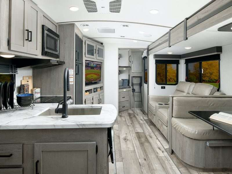 A view from the kitchen and living area of the Keystone Outback Ultra Lite 291UBH. The bunkhouse is tucked in the rear of this ultra lightweight travel trailer.