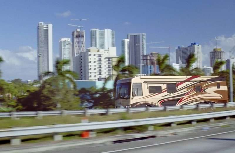 A Class A RV travels on a road lined with palm trees against a city skyscape in the background.