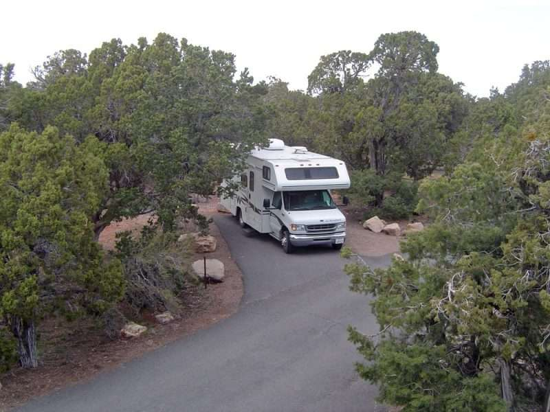 A Class C RV is parked on a campsite at Desert View Campground within Grand Canyon National Park. This site features paved road and campsite pad.