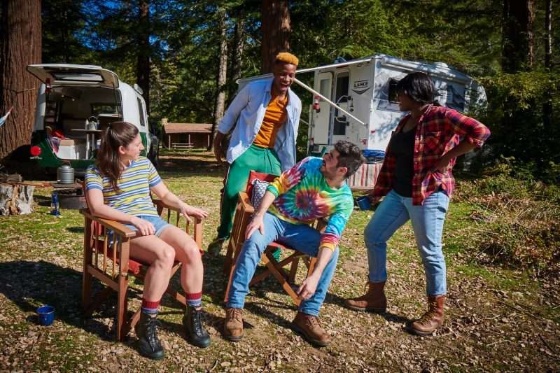 Four friends relax around a campsite where two small RVs are parked in the background.
