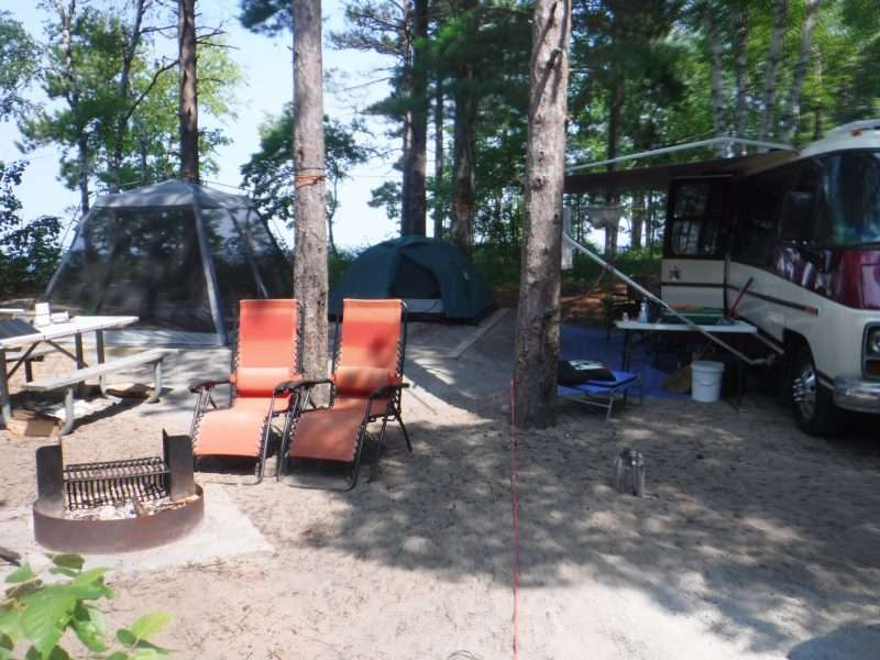 Twelvemile Beach Campground site 16 - showing a small RV and two tents on camp pad. Two red anti-gravity chairs sit next to a fire pit on the campsite.