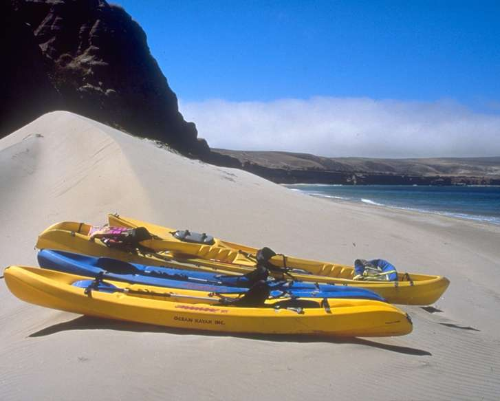Bright yellow and blue kayaks sit on the sand at Water Canyon Beach.