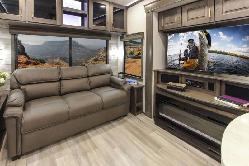 The living area of this fifth wheel RV includes a large sofa, LED TV,  and fireplace.