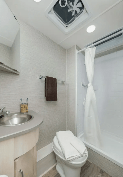 The bathroom of the Winnebago Outlook 22E includes a large shower, corner sink and vanity, plus toilet.