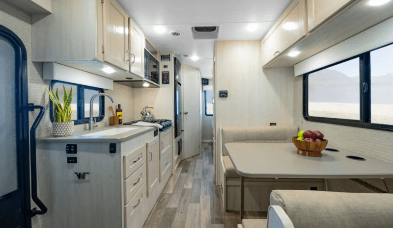 An interior view from the front of the Winnebago Outlook looking towards the back of the RV. The galley kitchen is on the passenger side and across from a dinette booth.