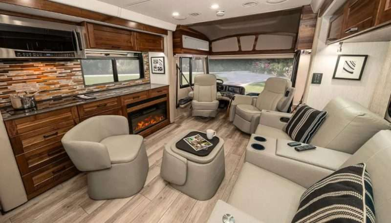 The living room of the Winnebago Journey includes multiple seating options: swivel chairs, theatre-style seating, and two chottomans.