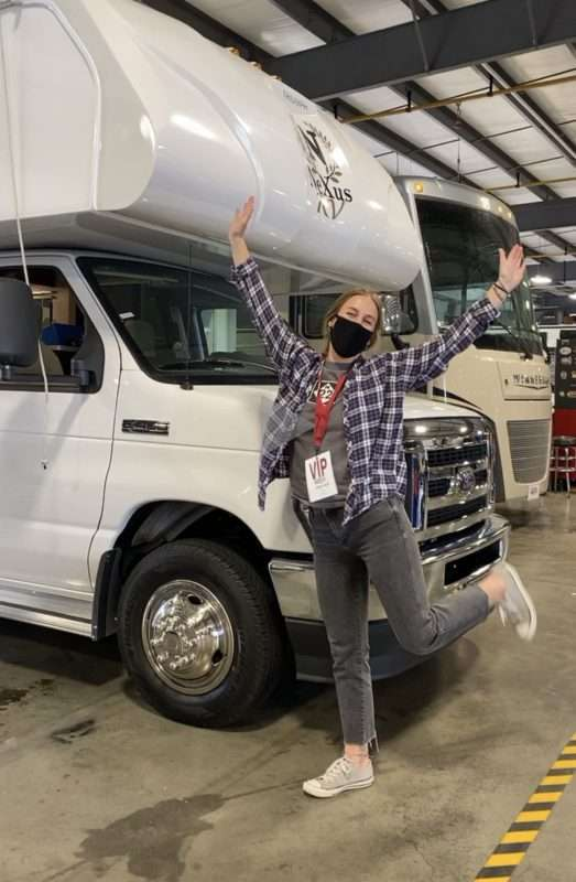 A young blond woman wearing a flannel shirt, faded black jeans and a black face mask, raises her arms and poses in front of a class C motorhome parked in a garage with the brand name Nexus on the front.