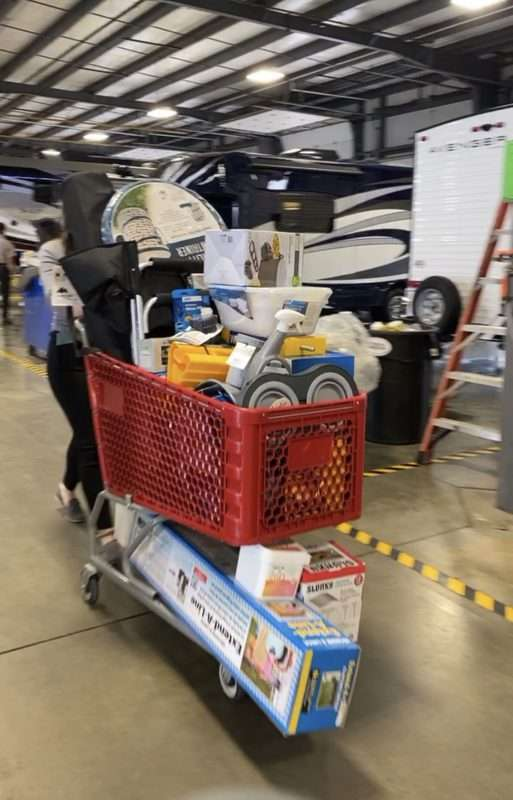 A red shopping cart filled with RV and camping accessories is pushed along a concrete floor in a large garage. There are multiple RVs in the background.