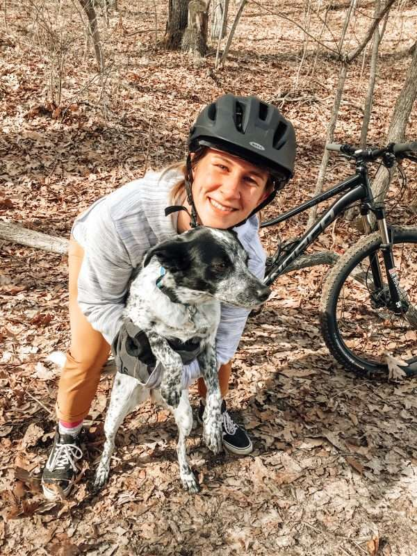 A young blond woman and a black and white dog pose in front of a black mountain bike on a forest trail covered with dry, fallen leaves.