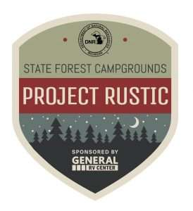The Project Rustic logo is an olive green badge with a red band across the middle that reads Project Rustic. At the bottom of the badge is an illustrated forest scene with trees silhouetted against a starry sky with a moon.