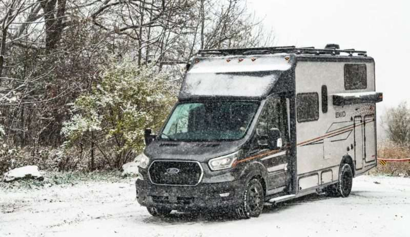A Winnebago EKKO motorhome is parked outside on a snowy day. The ground and trees in the background are covered with a thin layer of fresh white snow.