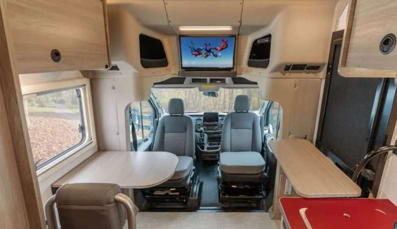 The interior of the Winnebago EKKO motorhome. The cab seats are swiveled around to face the galley and living area.