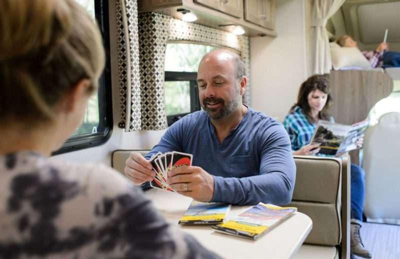 A family of four - mom, dad, and two daughters - relaxes inside their RV. Dad is playing a card game with the younger daughter at the dinette, while mom reads a magazine on the couch. The elder daughter is relaxing in the above cab loft.