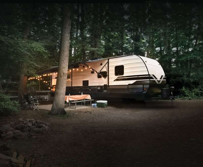 A travel trailer is parked on a campsite surrounded by tall, lush trees. The RV has its awning extended over a concrete pad with a picnic table.