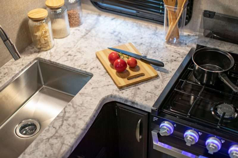 A closeup photo of an RV kitchen shows a corner of the skin and part of the RV's three-burner stove. Three bright red tomatoes sit next to a wooden cutting board and knife.