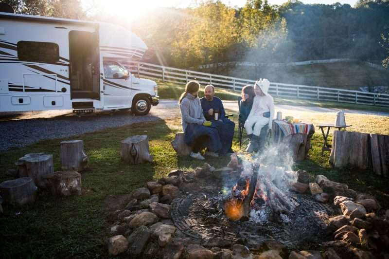 A family of four - mom, dad, and two daughters - sits around a campfire in front of their RV on a chilly morning. Everyone is bundled up in warm layers and the heat from the fire is steaming in the cool morning air.