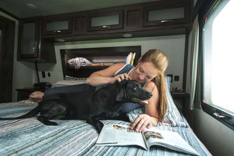 A woman and her dog relax together on a bed inside an RV.