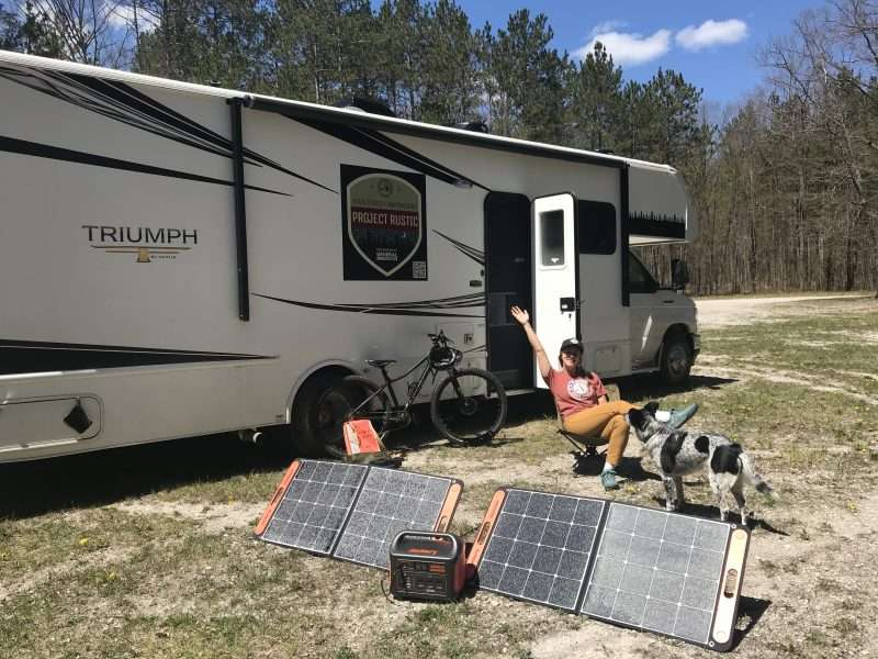 A young woman sits outside a Class C motorhome with her dog. She is sitting near her portable solar power setup which uses two large, folding solar panels to charge a lithium battery.