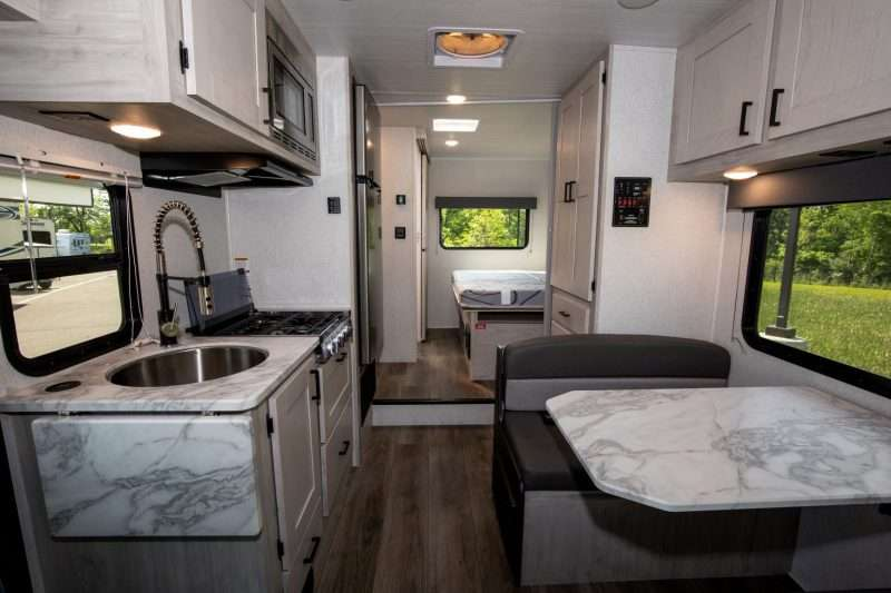 The interior of the Entrada 2200S class c motorhome features a light gray and white color palette. The counters and dinette table are marbled white and gray to compliment the hardwood cabinetry, while the dark gray fabric of the dinette seating provides contrast.