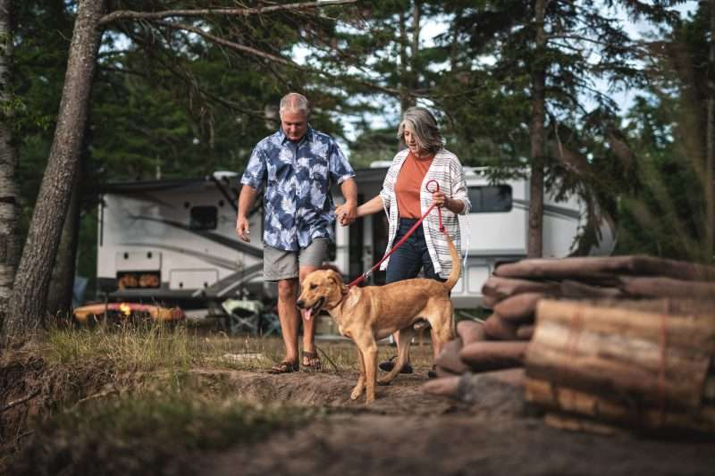 A man and woman walk a dog on a leash outside of their RV.