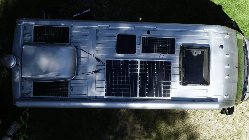 A photo from above shows the roof a Class B motorhome with five RV solar panels and one cargo container.