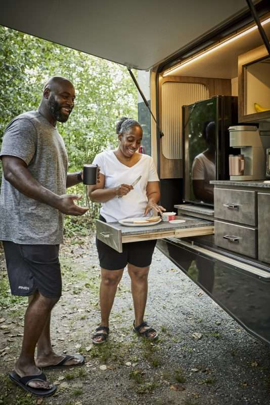 A man and woman making breakfast with their RV's outdoor kitchen.