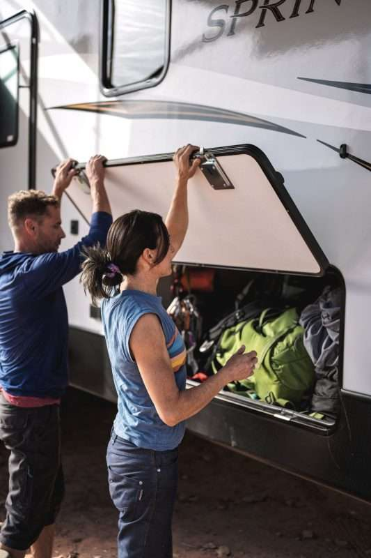 A man and woman pack an RV with gear.