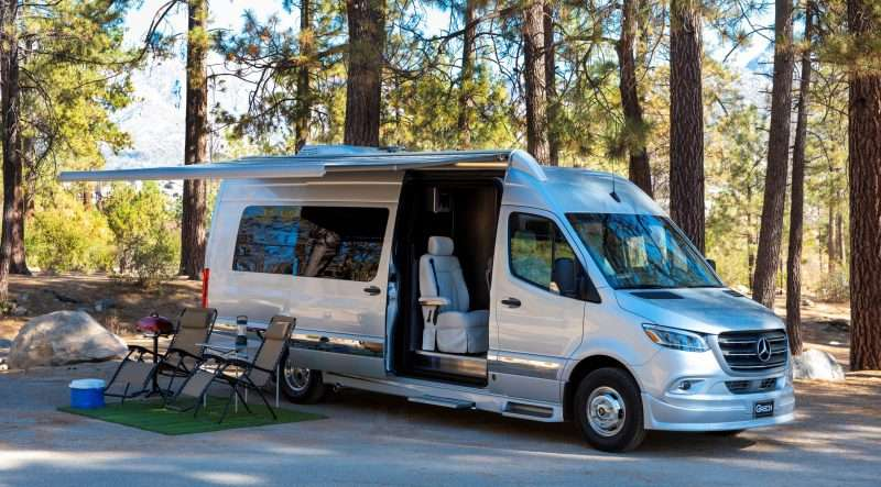 A silver Grech Strada Class B RV is parked at a wooded campsite with its awning extended. Below the awning, there are two lounge chairs, a grill, cooler, and folding table with a lantern set up.