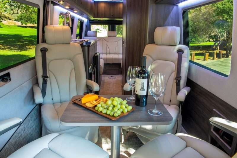 The forward lounge area of the Strada Class B motorhome has four chairs with a removable table. The table is set with a snack board featuring yellow cheese, crackers, and green grapes. There's also a bottle of wine and two wine glasses set out.