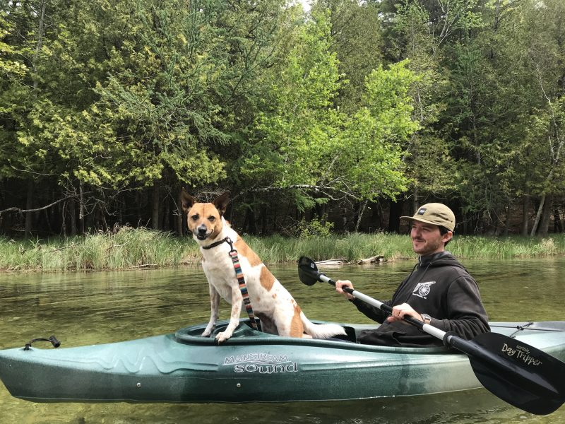 A man kayaks with his dog. The dog is standing up to look out over the water and towards the camera.