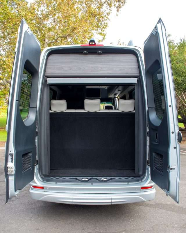The rear doors of the Strada Class B motorhome are opened to show a large cargo area behind the rear seats.