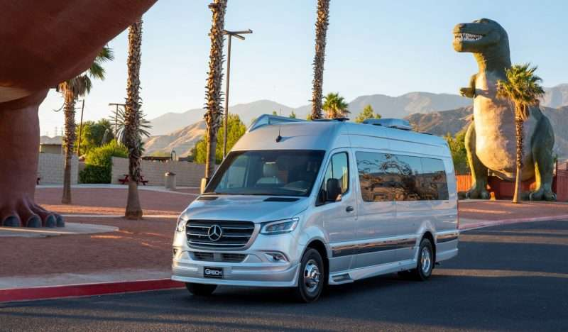 A sliver Grech Strada Class B motorhome on a road. There are tall palm trees and a sculpture of a tyrannosaurus rex dinosaur near the RV. Mountains are visible in the distance.
